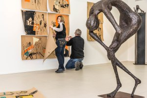 "Artists Tania Smith and Allan O'Loughlin hanging Tania's works for their exhibition ""Go Figure"""